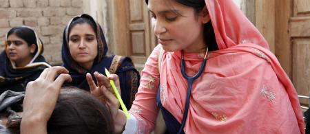 A doctor examines a woman patient at a mobile health clinic in Pakistan