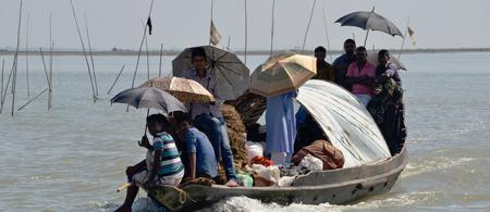 People with umbrellas on a crowded small boat on a river. Picture to illustrate that mental health is important for Trapped Populations.